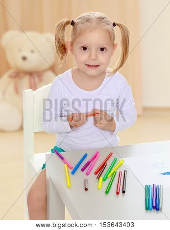 Pretty little blonde girl drawing with markers at the table.Girl holding in hands blue marker.The concept of preschool development of the child , against a child's room where in the background a Teddy