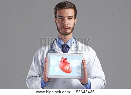 Cardiologist holding tablet with heart on screen against gray background. Health care concept.