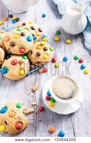 Homemade cookies with colorful chocolate candies with cup coffee on old white wooden table.