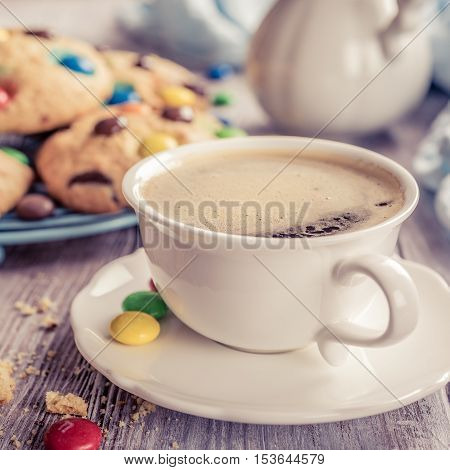 Cup coffee with homemade cookies with colorful chocolate candies on old white wooden table. Retro style toned.
