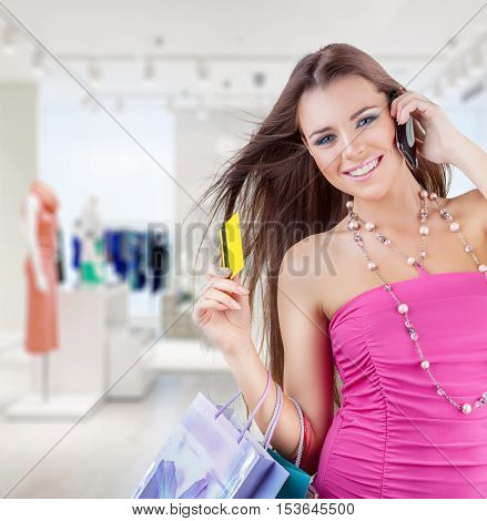 A smiling woman holding a credit card and talking on the mobile phone in the mall