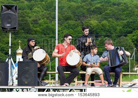ADYGEA RUSSIA - JULY 25 2015: Adyghe musical ensemble in the Circassian national costumes playing on stage on a background of green forest on ethnic festival in the mountains of Adygea
