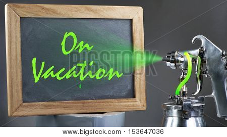 Spray painting a on vacation sign with green paint..