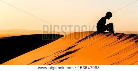 Meditating Young Man Sitting On Top Of A Dune Of Sahara