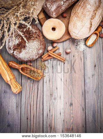 Fresh crispy breads baking of loaf and sweet donut on old wooden plate in rustic style copyspace