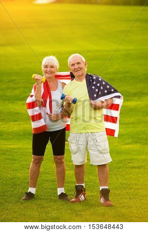 Couple wrapped in American flag. Senior people holding dumbbells. Strength and pride of citizens. New victories await.