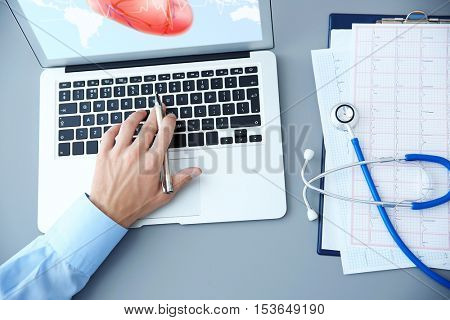 Cardiologist working with laptop at office. Health care concept.