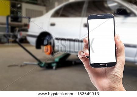 Hand holding blank screen mobile phone with inside car garage with repair service technicians for background and design