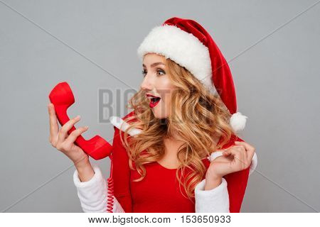 Amazed pretty young woman in santa costume with hat holding telephone receiver over grey background