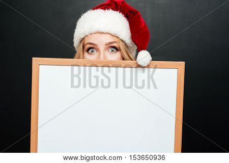 Cute young woman in santa claus hat hiding face behind blank white board