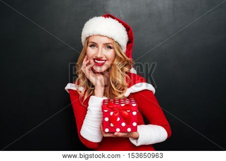 Cheerful charming young woman in santa claus hat holding present box