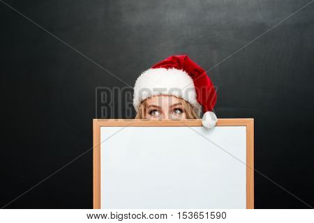 Amusing shy girl in santa claus hat hiding behind blank white board