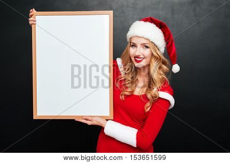 Cheerful pretty young woman in santa claus hat standing and holding blank white board