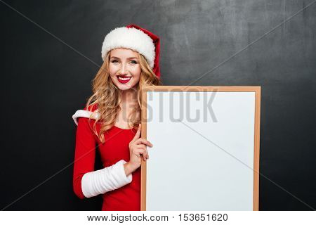 Happy cute young woman in santa claus hat holding blank white board
