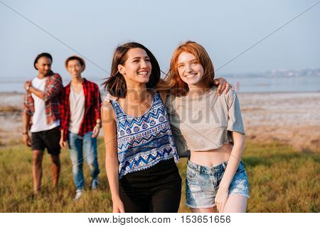 Two cheerful young men and women walking and laughing outdoors