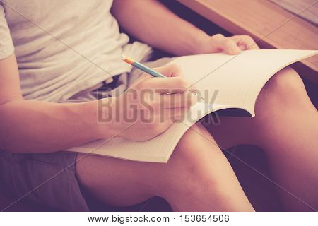 young man holding pencil on the right hand and writing in blank notebook on his lap while sitting on the floor