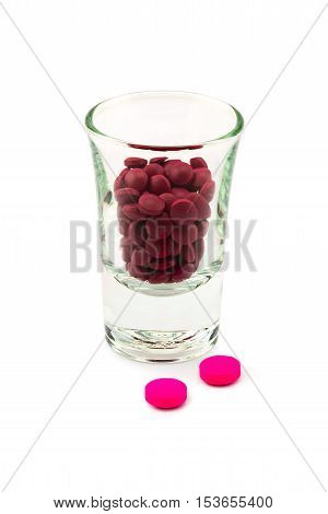 Pills of two kinds of medicine and small glass on white background