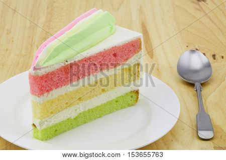 Layer cake on a white plate with a small spoon place on wooden table