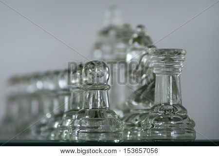 Closeup of a set of clear glass pieces on a chess board. Shallow depth of field only the front pieces in focus