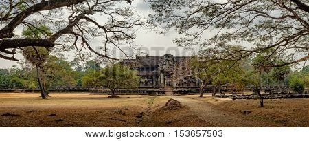 Ancient ruins of temple complex Angkor Wat surrounded by old tropical trees Siem Reap Cambodia.