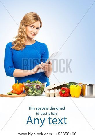 Young and beautiful housewife woman cooking in a kitchen using tablet with some free space.