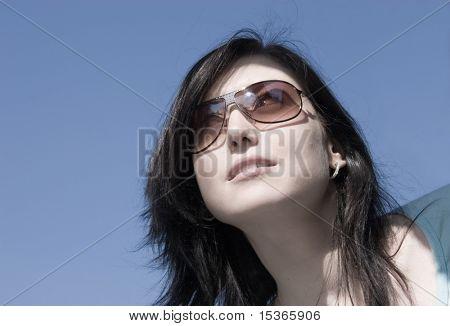 Skittish girl look. On blue sky background.