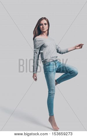 Casual style. Full length studio shot of attractive young woman in casual wear standing on one leg and looking at camera