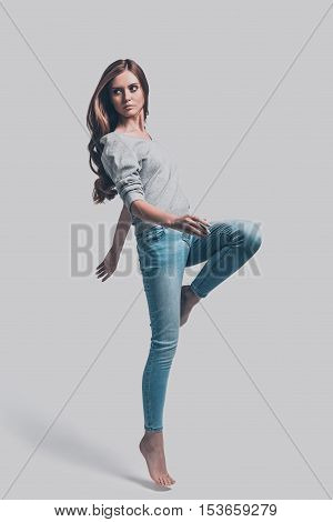 Slim and beautiful. Full length studio shot of attractive young woman in casual wear standing on one leg and looking away
