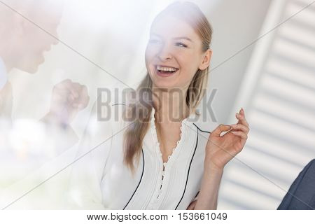 Smiling young businesswoman talking with male colleague in office