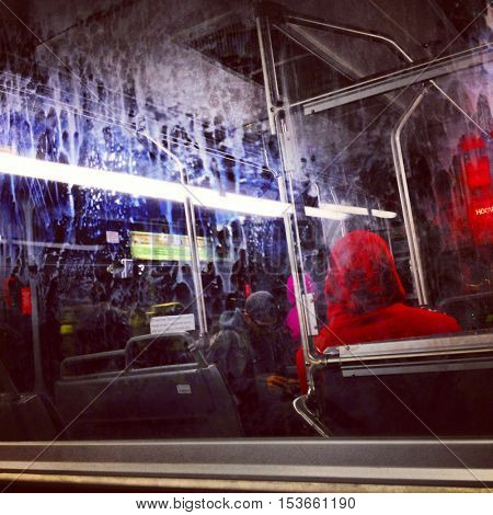 Interior or a dirty inner city bus with grime and filth on the divider glass