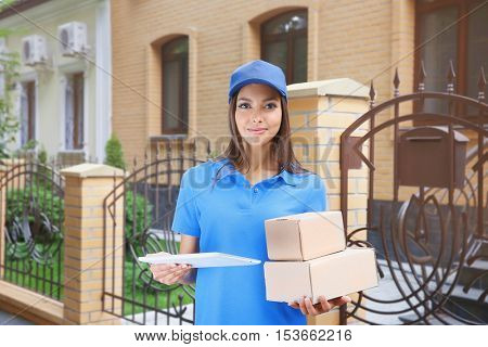 Female courier in uniform delivering parcels outdoor