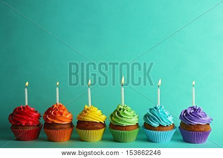 Fresh tasty cupcakes on turquoise background