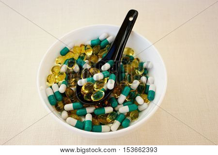 A scattering of different  tablets. Pills in a bowl on a woven background. Advertising a Healthy lifestyle, but also the possibility of  addiction to the medication and excess dosage. Horizontal.