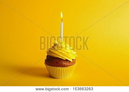 Fresh tasty cupcake with candle on yellow background