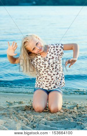 girl sitting on her knees on the sand near the water a summer day
