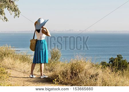 Young woman (brunette) in a blue skirt and hat looks at sea. Selective focus.