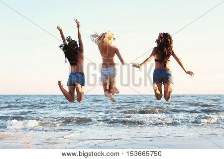 Happy girls jumping on beach