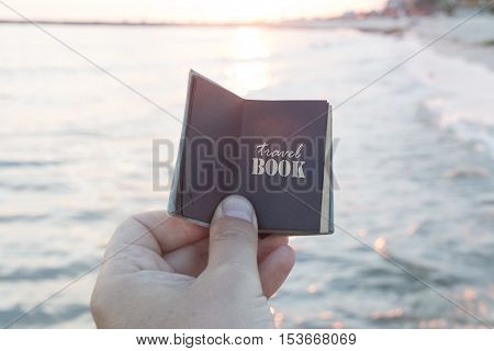 Hand holding a book with the inscription travel book
