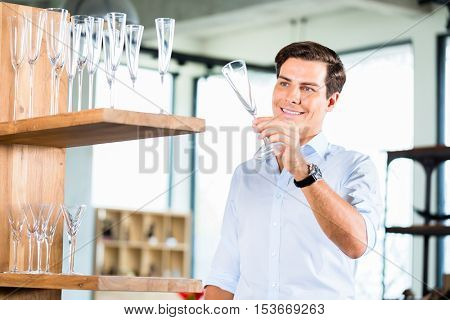 Man in furniture store choosing glasses standing in wooden shelf