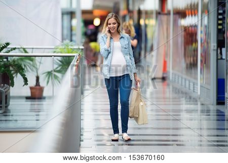Beautiful young pregnant woman holding smart phone, making phone call, in shopping center, walking