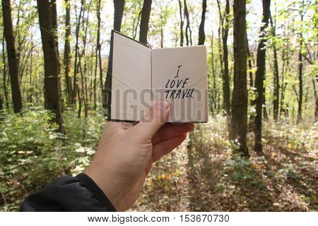 I love travel idea, hand holding a book with text