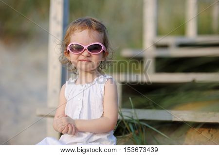 Adorable Toddler Girl Sitting On The Stairs