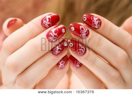 Red woman nails with decorations.