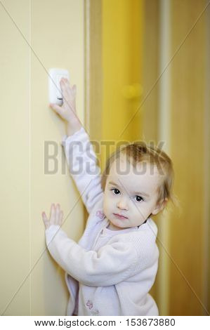 Adorable Girl Turning Off The Light-switch