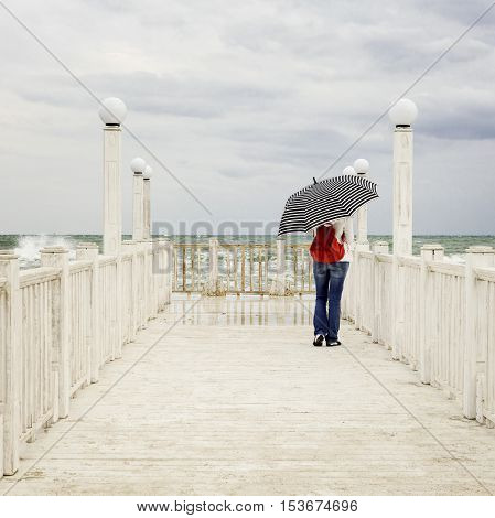 Young girl (brunette) in jeans with a red backpack and a striped umbrella stands on the pier and looking at sea storm. Selective focus.