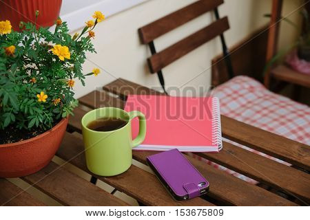 home office on the terrace, close-up, table, notebook, coffee mug