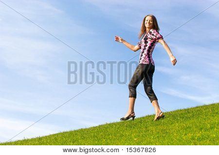 Jovem feliz vai para baixo de uma colina.