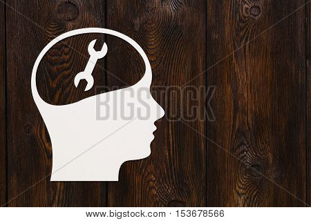 Paper head with wrench or spanner sign inside. Repair concept. Abstract conceptual image with copyspace. Dark wooden background