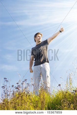 Joyful man showing excellent sign. Bright sun with rays.