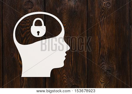 Paper head with padlock inside. Concept. Abstract conceptual image with copyspace. Dark wooden background